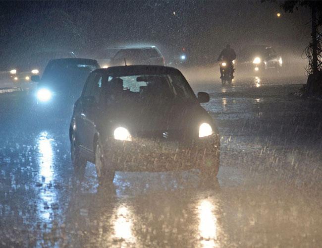 لاہور:شہر میں موسلادھار بارش کے دوران ٹریفک سڑک پر رواں دواں ہے
