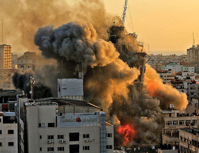 غزہ:اسرائیلی فوج کی فضائی بمباری سے عمارت کے تباہ ہوتے ہوئے دھویں کے بادل اٹھتے ہوئے