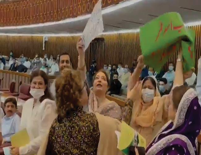 قومی اسمبلی میں حکومتی خواتین ارکان اپوزیشن سے پلے کارڈ چھیننے کی کوشش کرتے ہوئے