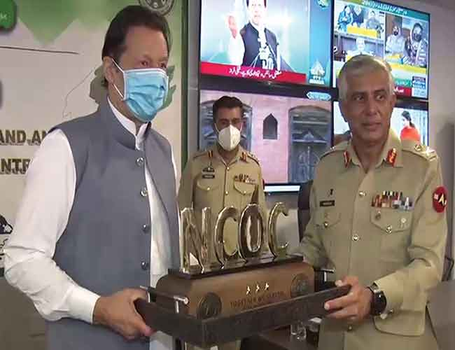 اسلام آباد :وزیر اعظم عمران خان لیفٹیننٹ جنرل حمود الزمان کو این سی او سی  میں شاندار خدمات پر یادگاری تحفہ دیتے ہوئے